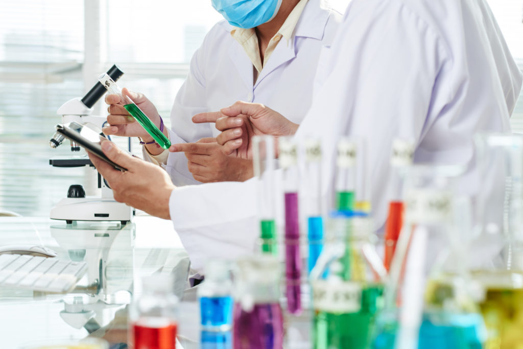 Close-up shot of unrecognizable chemists wearing white coats examining content of test tube and taking necessary notes with help of digital tablet while carrying out experiment